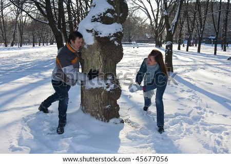 Young beautiful couple playing with snow in winter park. Sunny day. Looking to each other
