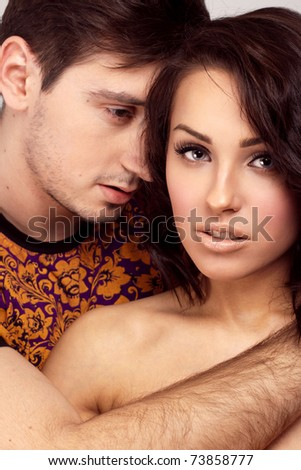 Young beautiful couple posing in the studio