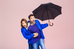 Young beautiful couple posing wearing one rain coat holding umbrella over light pink background.