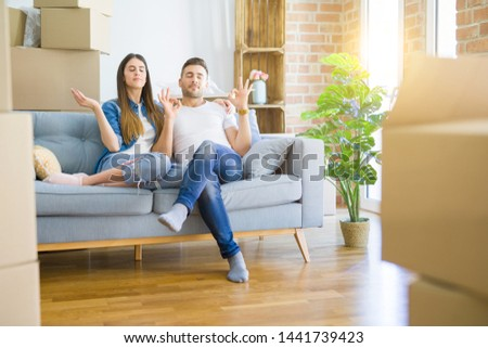 Young beautiful couple relaxing sitting on the sofa around boxes from moving to new house relax and smiling with eyes closed doing meditation gesture with fingers. Yoga concept.