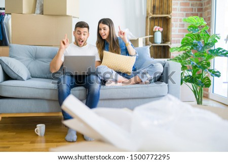 Young beautiful couple relaxing sitting on the sofa of new house using computer laptop surprised with an idea or question pointing finger with happy face, number one