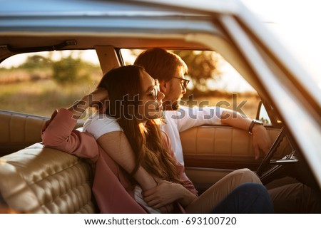 Young beautiful couple relaxing together while sitting inside a retro car