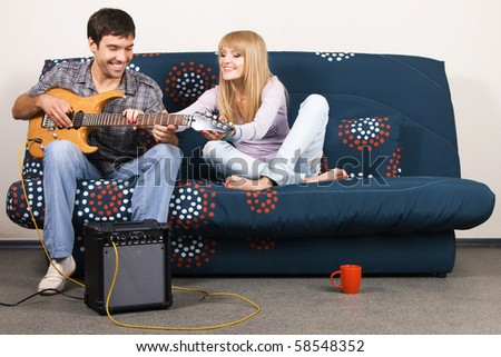 Young beautiful couple resting at home and playing electric guitar