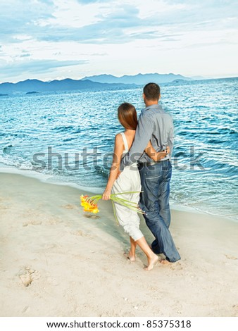Young beautiful couple walking near the ocean