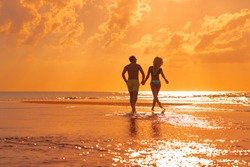 Young beautiful couple walks along the seashore at sunset. Honeymoon. Romantic trip.