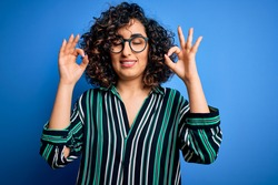 Young beautiful curly arab woman wearing striped shirt and glasses over blue background relax and smiling with eyes closed doing meditation gesture with fingers. Yoga concept.