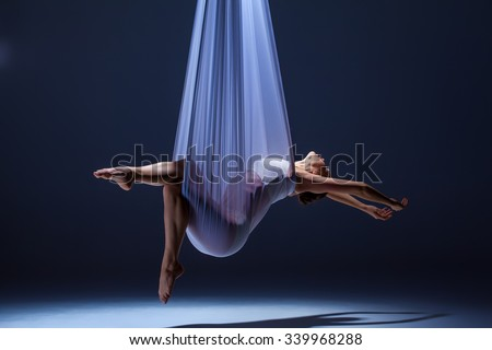 Young beautiful dancer in beige dress posing with  hammock fabric on gray studio background