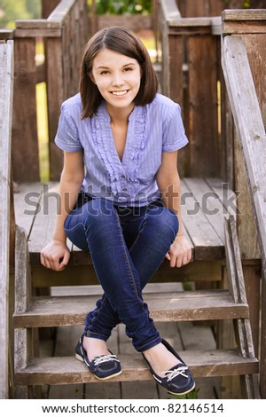Young beautiful dark-haired smiling woman wearing blue blouse and jeans sitting on wooden staircase at summer park.