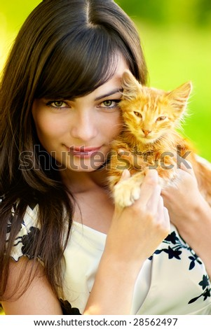 Young beautiful dark-haired woman holds in hands of red kitten.