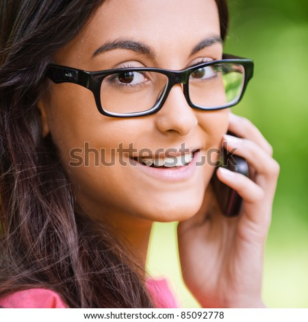 Young beautiful dark-haired woman in glasses black are right talks on cellular telephone and smiles, against green summer garden. - stock photo