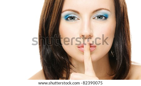 Young beautiful dark-haired woman with bared shoulders puts forefinger to lips as a sign of silence, isolated on white background.