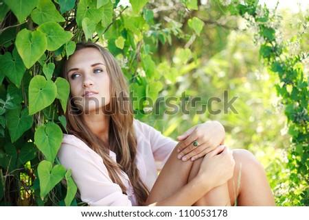 Young beautiful dreaming girl in green summer garden