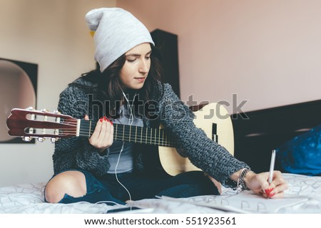 Young beautiful eastern woman sitting on her bed in the bedroom holding guitar composing a song - musician, songwriter, composer concept