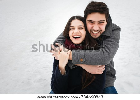 young beautiful enamored couple in winter hugging in snow, together