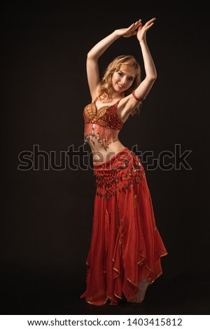 1eb6c87780dfa Young beautiful exotic eastern women performs belly dance in ethnic red  dress on gray background.