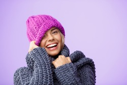 Young beautiful fair-haired girl in knited hat and sweater smiling winking looking at camera over violet background.
