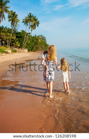 Young beautiful family of three walking along tropical beach