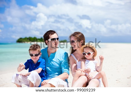 Young beautiful family with two kids sitting on tropical vacation