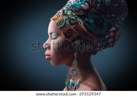 young beautiful fashion model with traditional african style with scarf, earrings and makeup on dark blue background.  \ Developed from RAW, edited with special care and attention.