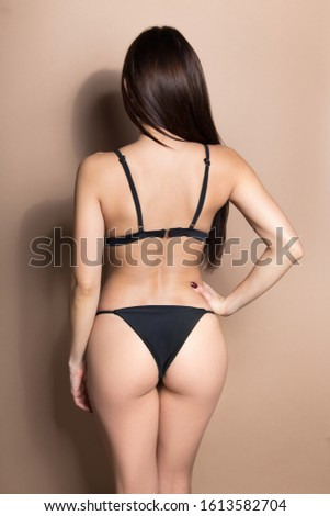 Young beautiful fashion model woman in lingerie. Studio photo of posing sexy woman with nice lingerie on beige background.