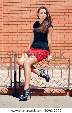 Young beautiful fashion woman sitting on iron fence against brick wall