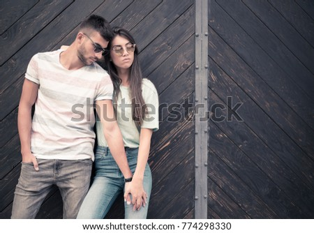 Young beautiful fashionable couple posing against wooden gate holding hands