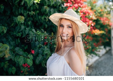 Young beautiful fashionable woman wearing straw hatl posing in street with flowering trees. Summer fashion concept. Stok fotoğraf ©