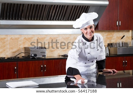 young beautiful female chef cleaning commercial kitchen - stock photo