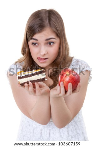 Young beautiful female choose from sweet cake and red apple, on white background