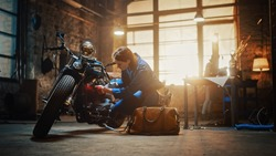 Young Beautiful Female Mechanic is Working on a Custom Bobber Motorcycle. Talented Girl Wearing a Blue Jumpsuit. She Uses a Ratchet Spanner to Tighten Nut Bolts. Creative Authentic Workshop Garage.