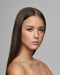 Young beautiful female model close-up studio beauty portrait. Girl with natural make-up and long brunette straight hair. Calm woman looking at you