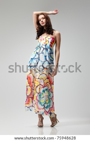 Young beautiful female model in colorful dress on gray background