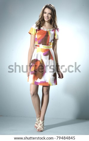 Young beautiful female model in colorful dress on light background