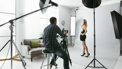 Young beautiful female model posing for a photo shoot in a studio, a photographer is shooting with a digital camera
