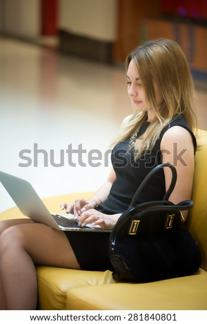 Young beautiful female sitting on yellow coach working on laptop in public wifi area, typing
