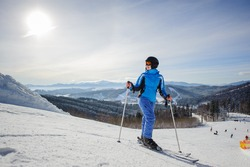 Young beautiful female skier on the middle of ski slope looking to the sun. Woman at ski resort wearing helmet blue ski suit and goggles. Winter sports concept. Carpathian Mountains, Bukovel, Ukraine