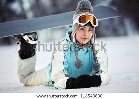 Young beautiful female snowboarder resting on ski slope, she's lying on front and smiling, close up