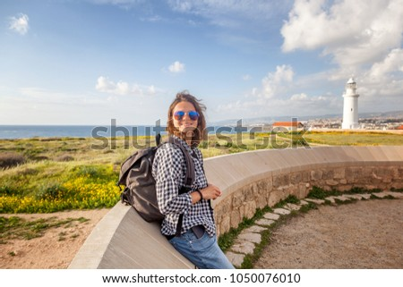 Young beautiful female tourist girl on a background of beautiful scenery, the seas and with a lighthouse. Travel to Cyprus