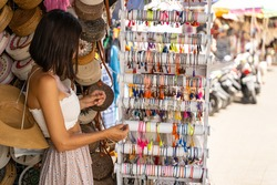 Young beautiful female tourist is choosing souvenirs in street shop and looking at colour bracelets. Local souvenir concept