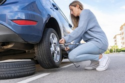 Young beautiful female using force trying to unscrew the wheel bolts nuts with the car jacked up changing wheel..Replacement winter summer season tires ,repairing and maintenance concept lifestyle