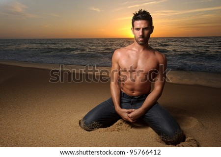 young beautiful fit man at the beach with sunset on his back