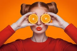 Young beautiful funny fashion model with orange slice on background. with makeup and hairstyle and freckles.