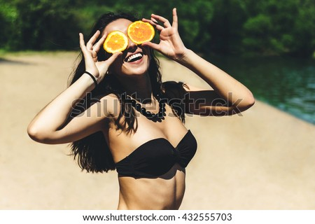 Stock Photo Young beautiful funny summer model holding orange in front eyes with smile and laugh on the beach in bikini sunny summer day. Vacation holiday relax concept.