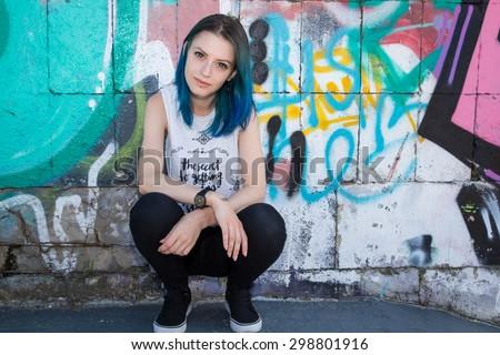 Stock Photo Young beautiful girl agains graffiti wall