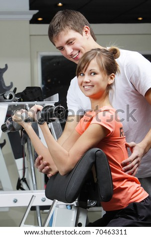 Young beautiful girl and her trainer in fitness club