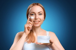 Young beautiful girl applies cosmetic cream to her face. Caring for the skin at a young age. Happy woman uses skin care product. A jar of face cream in the hands of a beautiful lady