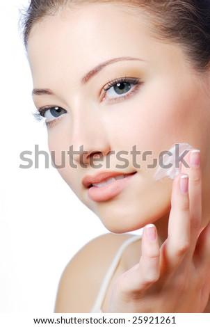 Young beautiful girl applying cream on her cheek