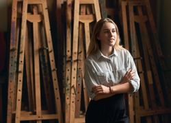 Young beautiful girl art or architecture student is dreaming of her future on old wooden easels background in studio