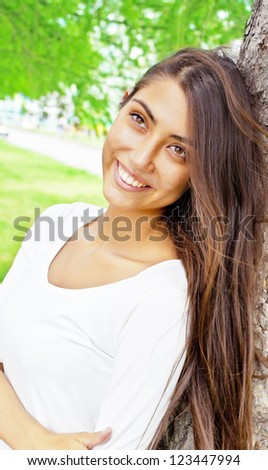 Young beautiful girl based on the tree and smiles.