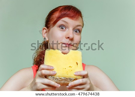 young beautiful girl bites cheddar cheese on green background